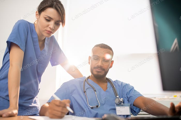 One of young clinicians showing his notes to colleague during discussion