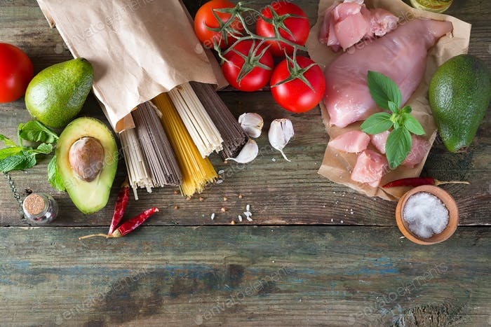 Italian food background with tomatoes, basil, spaghetti, olives, garlic, raw chicken meat