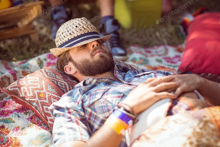 Handsome hipster relaxing on campsite at a music festival