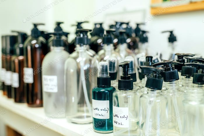 Different sizes pumping and spray bottles, recycling materials in a shop. Zero waste concept