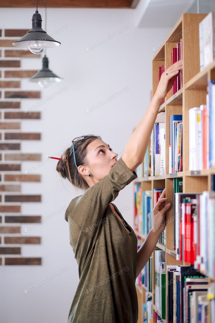 Young woman wearing glasses looking for a book on a bookshelf, i