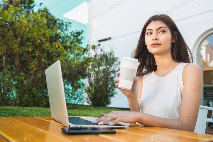 Young woman using laptop at coffee shop.