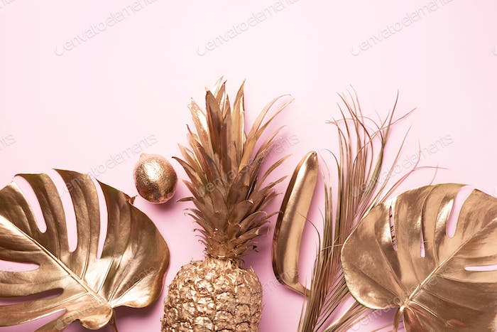 Golden exotic fruits, tropical palm, monstera leaves on pink background. Top view. Flat lay. Food