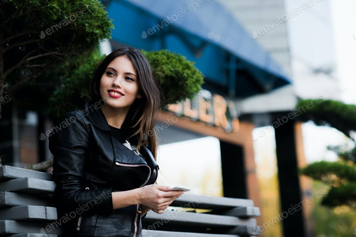 Smiling woman sending sms on the street