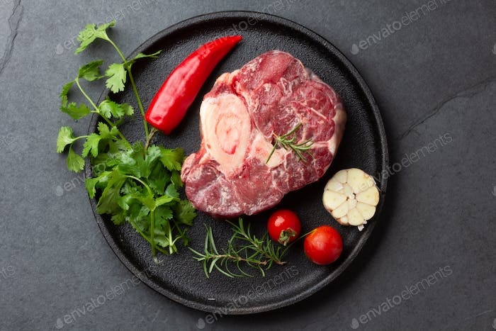 Raw fresh cross cut veal shank and meat cleaver for making Osso Buco on dark wooden background