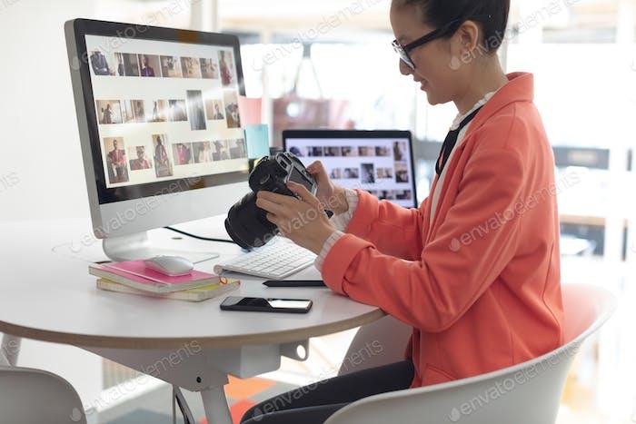 Asian female graphic designer looking photos in digital camera at desk