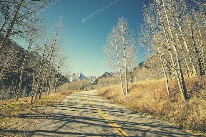 Retro old film stylized picture of a mountain road, travel conce