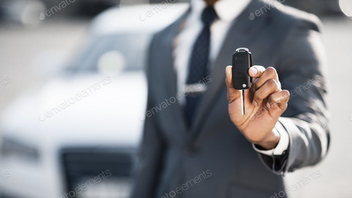 Businessman showing car key against luxury auto