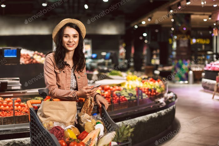Pretty smiling girl in hat with trolley full of products joyfull