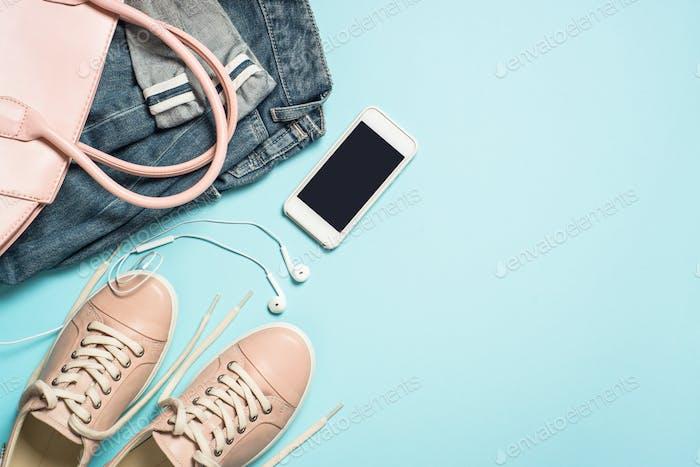 Woman fashion cloth set pink shoes, jeans, handbag, smartphone and perfume on blue background