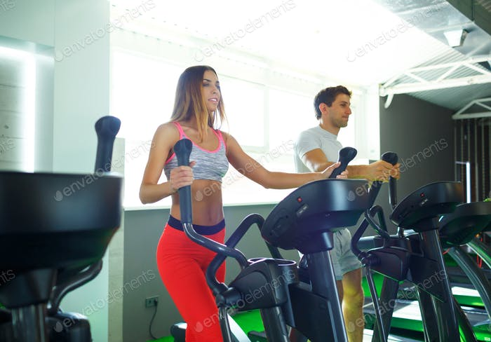 Athletic man and woman doing cardio training program in fitness