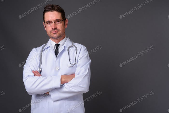 Handsome man doctor against gray background