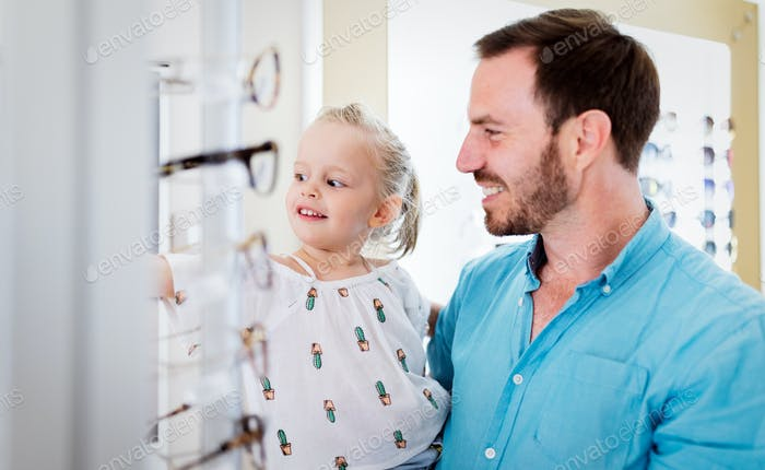 Health care, eyesight and vision concept. Little girl choosing glasses with father at optics store