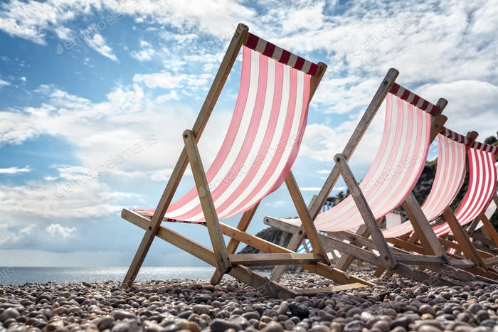 Deck chairs on the beach at the seaside summer vacation