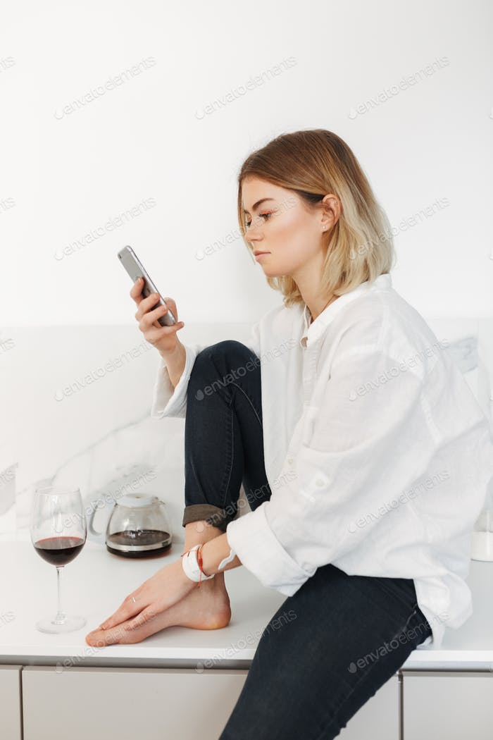 Young lady sitting on kitchen counter with cellphone in hand and glass of red wine near at home