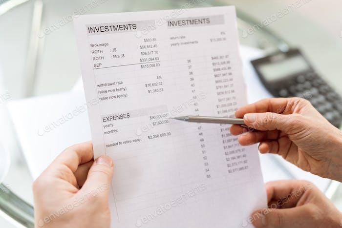 Menschliche Hand halten Stift, während zeigen auf Geldsumme in Finanzdokument
