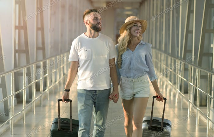 Millennial couple going in airport terminal with luggage
