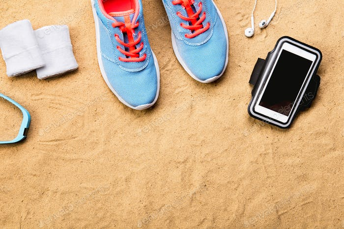 Sports shoes, earphones, smartphone against sand, studio shot.