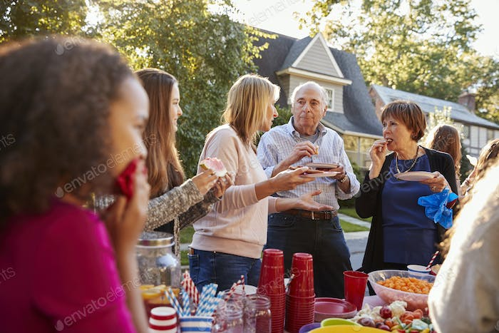 Neighbours talk and eat at a block party, close up