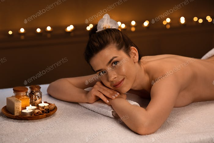 Smiling topless woman having aromatherapy session at spa