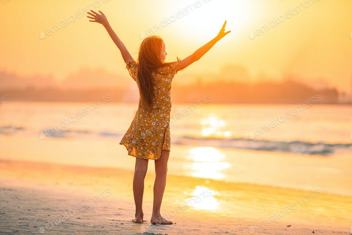 Adorable happy little girl on white beach at sunset