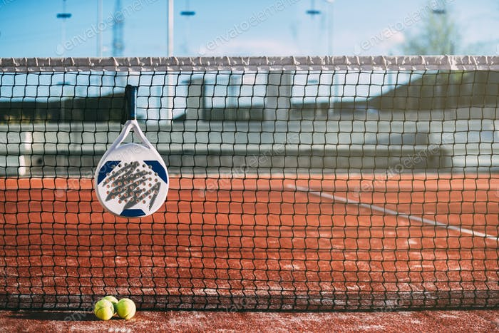 Padel blade racket hanging on the net
