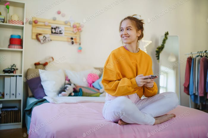Happy young female student sitting on bed, using smartphone