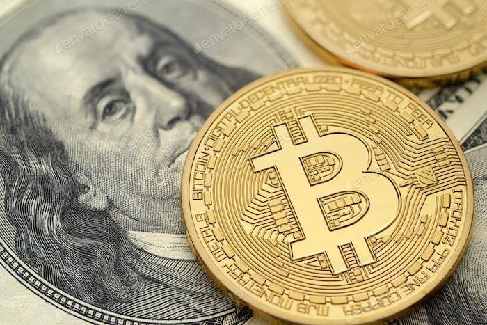 US hundred dollar bills and physical golden bitcoin