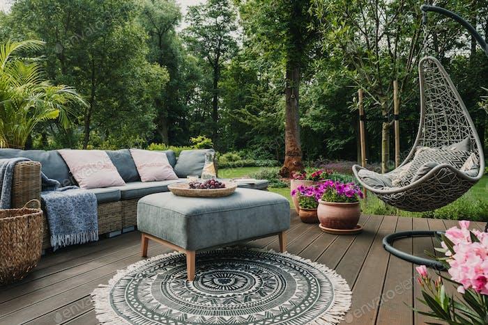 Patio de jardín decorado con sofá de mimbre escandinavo y mesa de centro