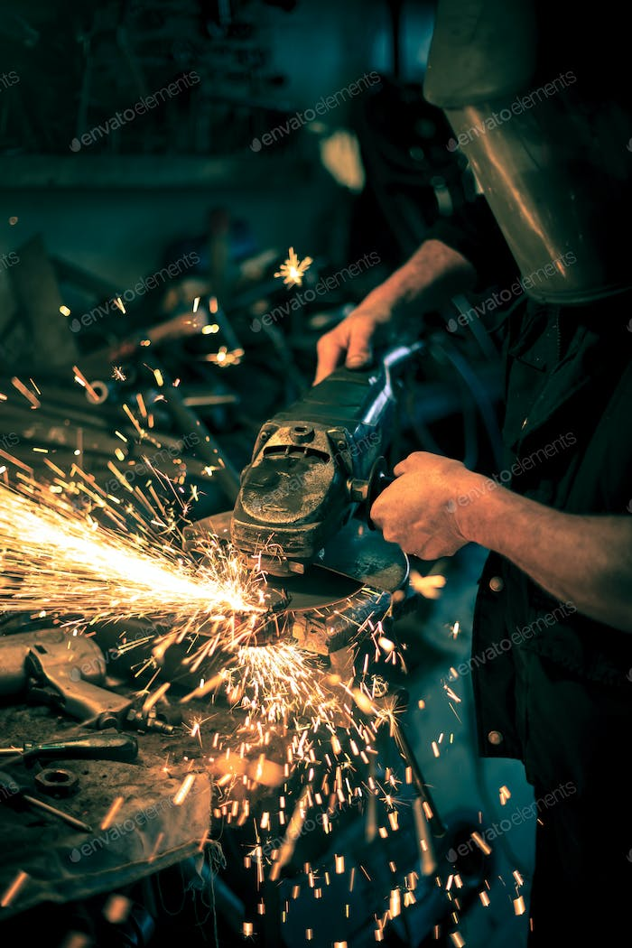 Metal grinding on steel spare part in workshop
