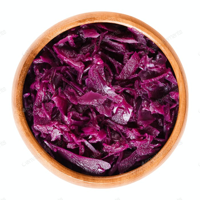 Cooked red cabbage in wooden bowl over white