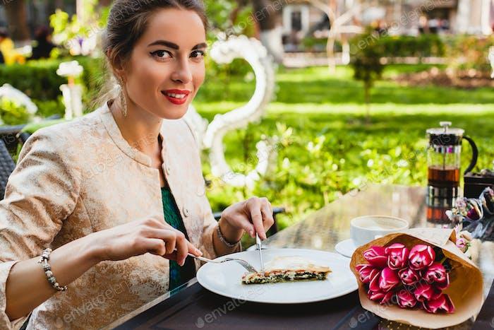 joven mujer elegante sentado en la cafetería, comiendo pastel sabroso