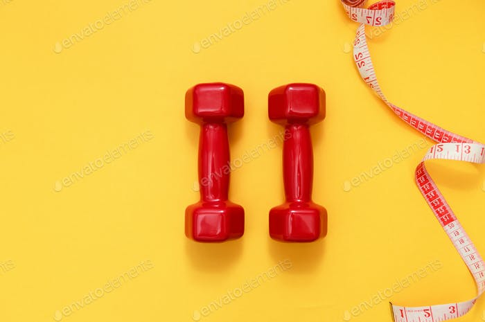 Two red dumbbells and tape measure. Fitness concept