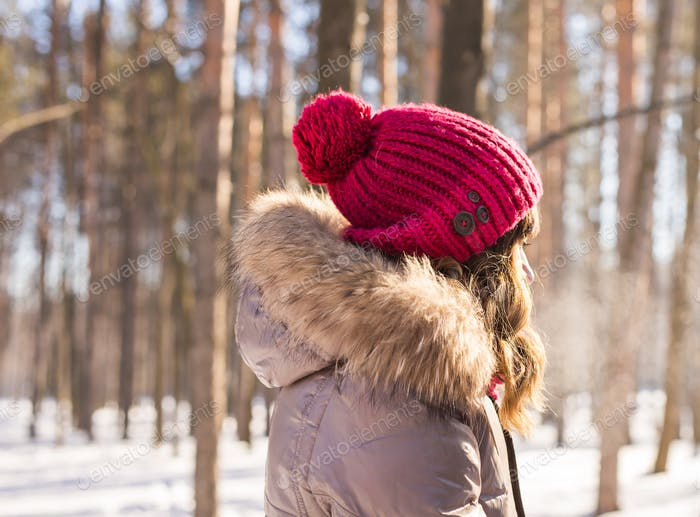 girl in a red winter hat view from the back