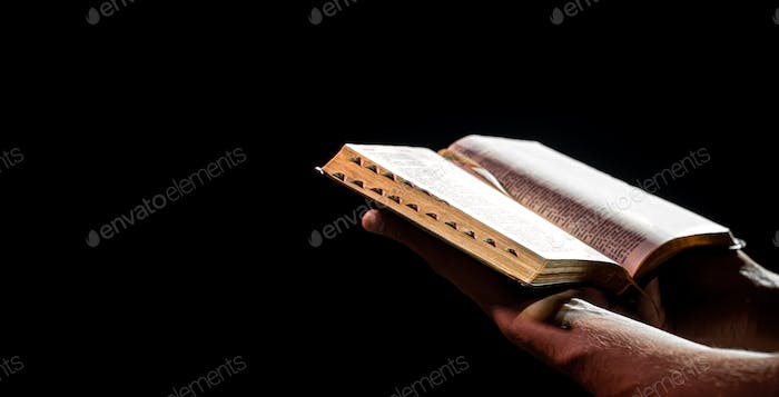 A man holds an open Bible. The concept of a relationship with God.