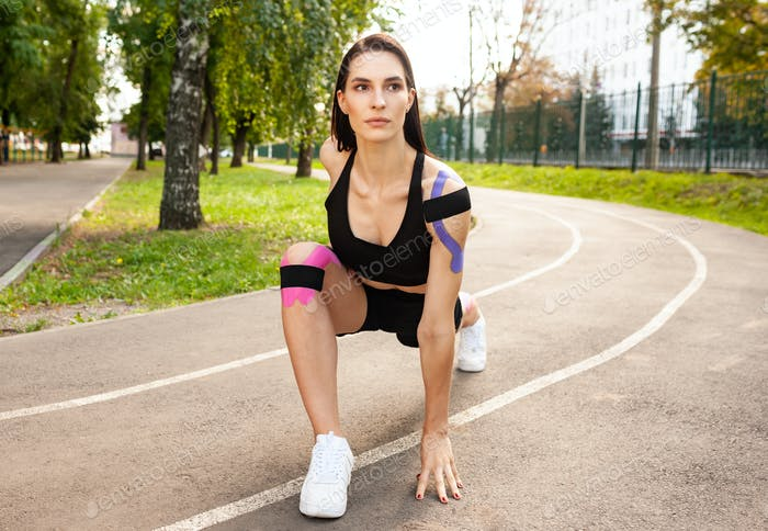 Flexible sportswoman with kinesiotaping practicing lunges outdoors