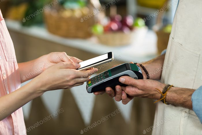 Frau, die eine Zahlung mit NFC-Technologie macht