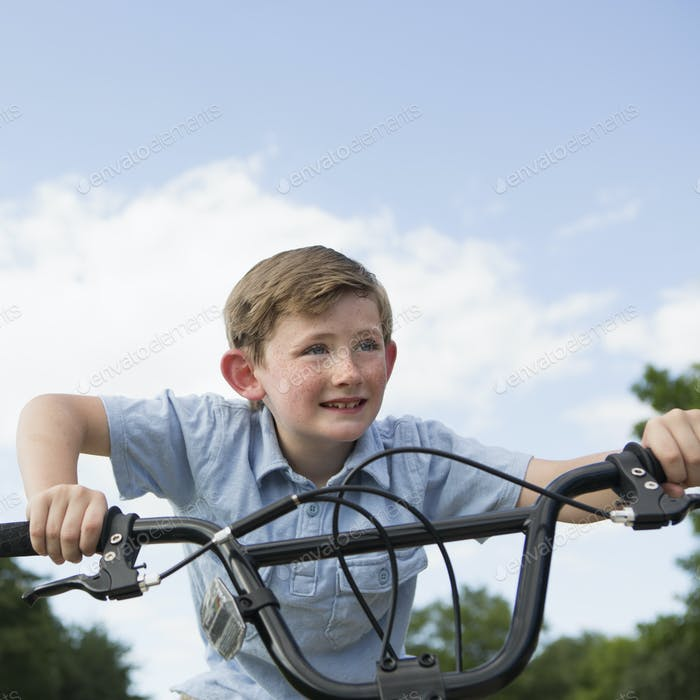 A young boy leaning over the handlebars of a bicycle.