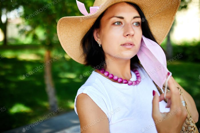 Portrait of woman in straw hat takes off pink protective mask