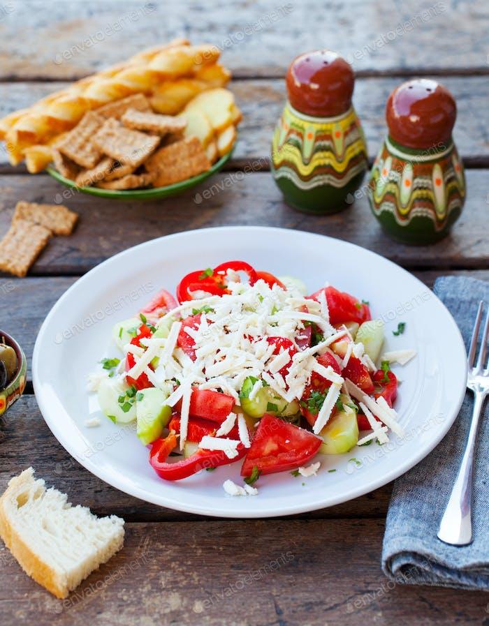 Vegetable Bulgarian Shopska salad. Grey wooden background.