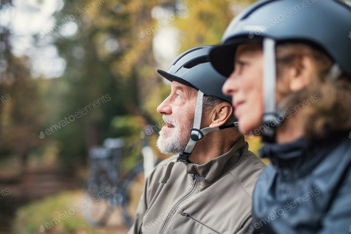A senior couple with bicycle helmet standing outdoors in park in autumn.