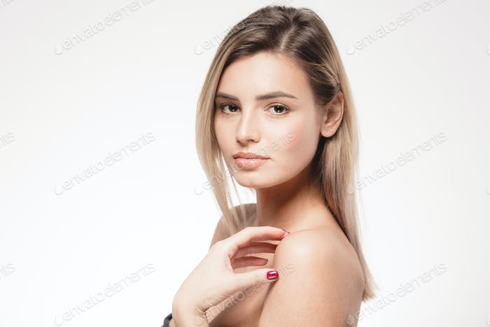 Blonde woman is touching her shoulders. Beauty portrait face looking camera isolated on white.