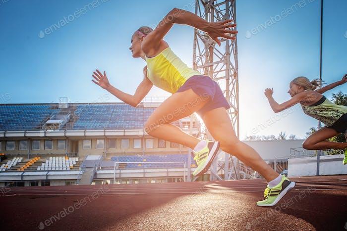 Two female sprinter athlete in the athletics stadium.