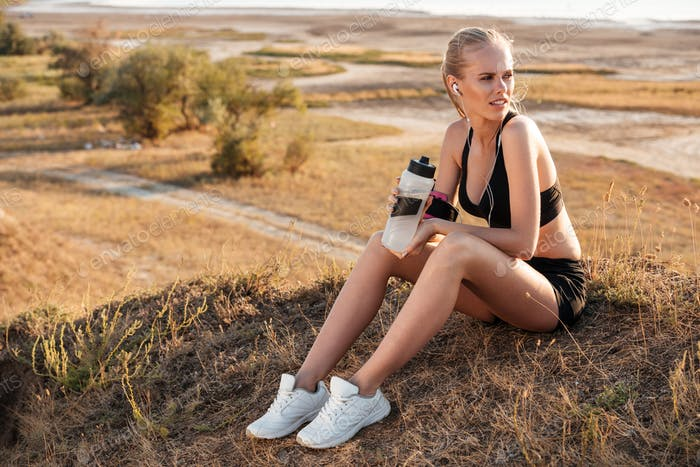 Fitness young woman resting and holding water bottle after jogging