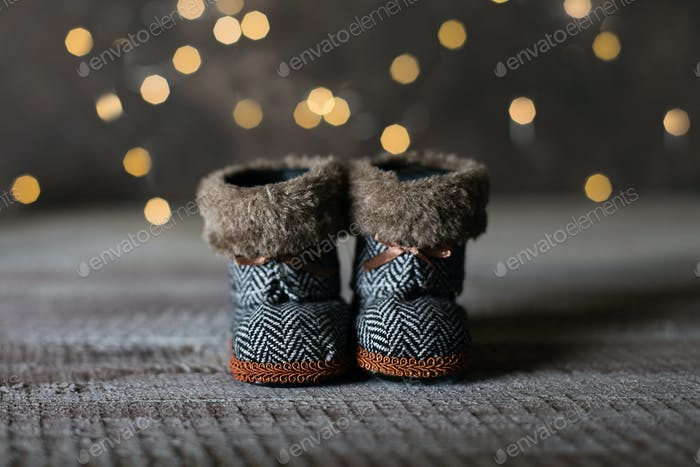Holiday Christmas Baby Toy Small Boots on Wooden Table Background. Cozy Concept.