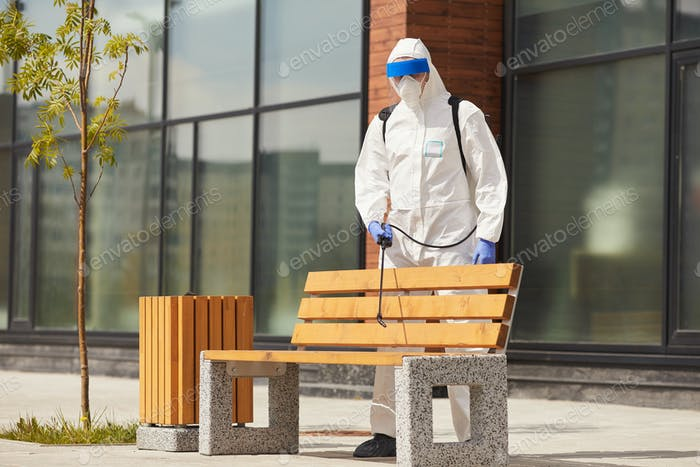 Worker Disinfecting Bench Outdoors