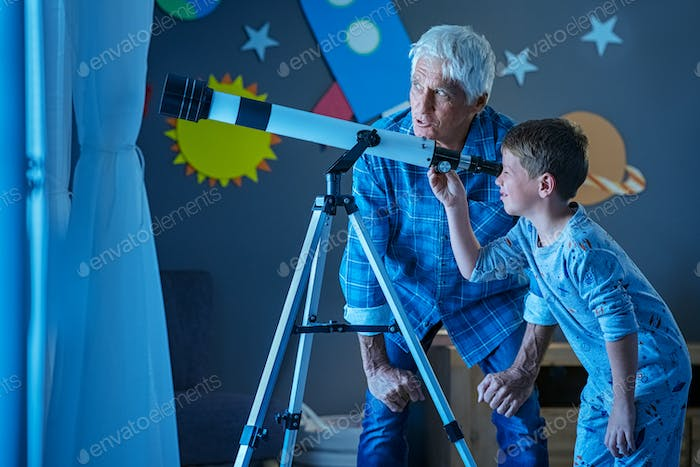 Child with grandfather using telescope during night