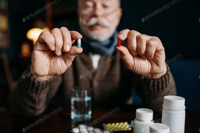 Elderly man holds pills in his hands