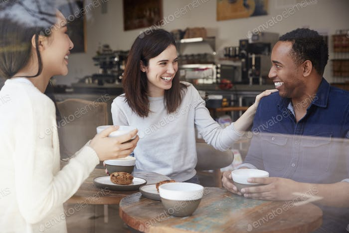 Three friends having coffee and laughing at a coffee shop