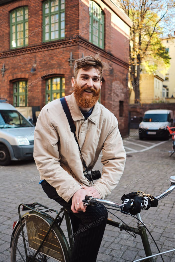 Young cheerful bearded man on old bicycle happily looking in camera on street